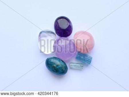 Tumbled Gems Of Various Colors. Amethyst, Rose Quartz, Apatite, Aventurine, Rock Crystal On White Ba