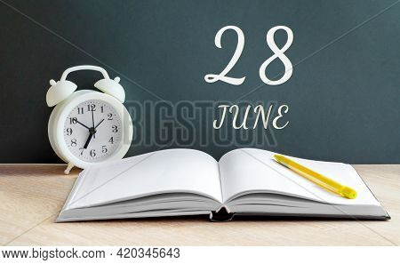 June 28. 28-th Day Of The Month, Calendar Date.a White Alarm Clock, An Open Notebook With Blank Page