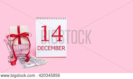14th Day Of December. A Gift Box In A Shopping Trolley, Dollars And A Calendar With The Date Of 14 D