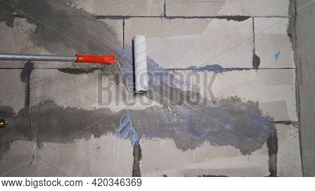 Painter Paints Wall With Paint Roller White. Painter Man At Work With A Paint Roller. The Worker Pri