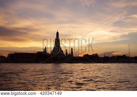 Silhouette Of Wat Arun Temple At Sunset On Chao Phraya River Landmark Of Bangkok, Thailand