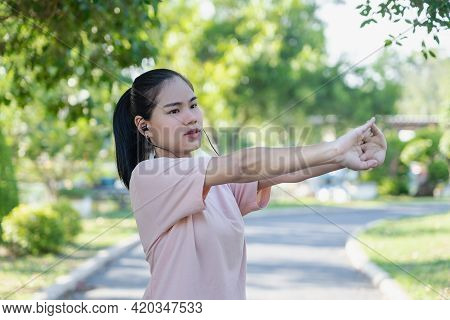 Happy Young Fitness Woman Doing Stretch Exercise Outdoors In Park. Asian Female Stretching Her Arms