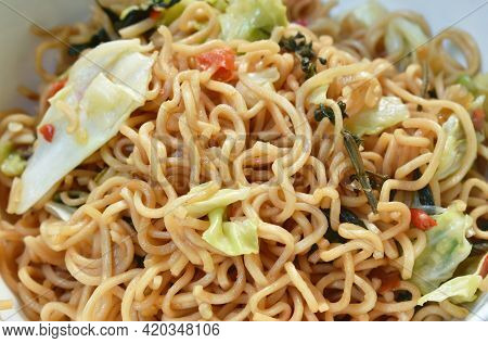 Spicy Fried Instant Noodles With Cabbage And Basil Leaf On Plate