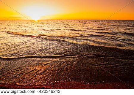 Sunset At Sea. Warm Sunny Sunset Over The Sea. Sea Waves. The Sun Sets Over The Horizon.