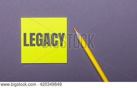 On A Gray Background, A Bright Yellow Pencil And A Yellow Sticker With The Word Legacy