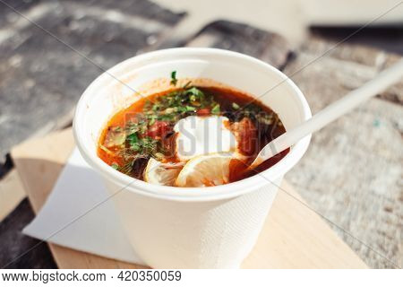 Close-up Of A Hodgepodge In A Disposable Paper Cup. The Concept Of Traditional Food And Foreign Cuis