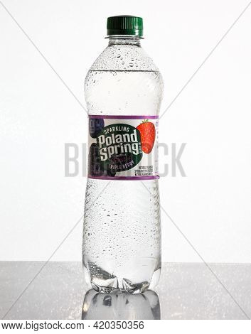 Bottle with sparkling Poland Spring with a teist triple berry on white background