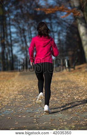Woman running in autumn park