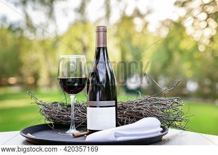 A Bottle Of Red Wine With A Full Glass Stands On The Grass In The Evening Light In The Rays Of The S