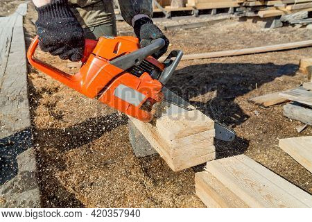 Close-up Of Woodcutter, Sawing Wooden Boards Chain Saw In Motion, Sawdust Fly To Sides. Chainsaw In