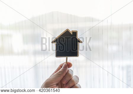 Real Estate Agent Holding House Shaped Wood(space For Text Input) On Blurred House Background.