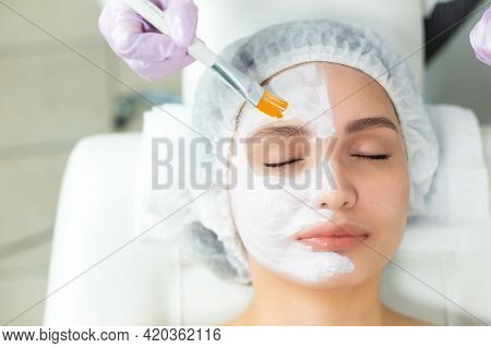 Facial Skin Care And Protection. A Young Woman At A Beauticians Appointment. The Specialist Applies