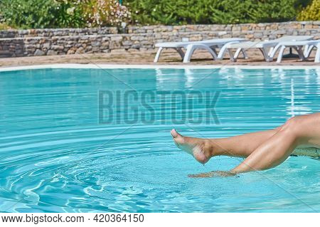 Closeup Of Female Barefoot Legs In Pool Splashing In Sunlight In Motion. Summertime Moments Concept