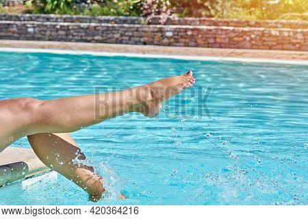 Female Barefoot Legs In Pool Splashing In Sunlight In Motion. Summertime Moments Concept