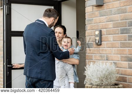 Housewife With Newborn Baby Staying In Front Of Entrance Door Of House And Greets A Husband And Dad