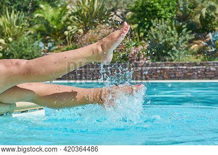 Suntanned Woman Legs Splashing In Swimming Pool, Motion Blur, Closeup