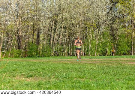 Young Sporty Tanned Girl Running In The Morning Green Park. A Woman In Short Sportswear Is Jogging W