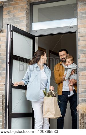 Young Parents With Newborn Kid Customer Order Food Delivery Online And Standing In Front Of The Hous