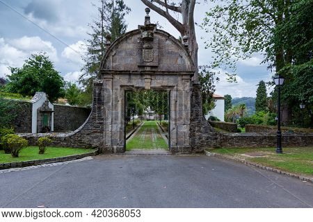 Front Entrance To Building In Galicia, Blue Sky With Few Walnut Trees And Grassy Yard