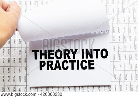 Notepad With Text Theory Into Practice On The Office Desk With Stationery. A Blank Notepad For Enter