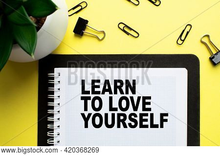 Notepad With Text Learn To Love Yourself On The Office Desk With A Plant, Stationery. A Blank Notepa