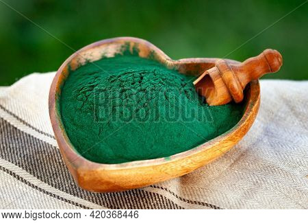 Ground Spirulina in bowl on textile background, top view on heart shape dish with superfood