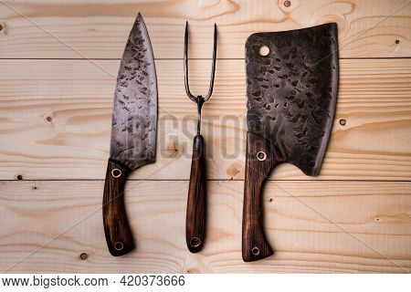 Antique Stylized Butcher's Set. Cleaver, Knife And Fork On A Wooden Background. View From Above