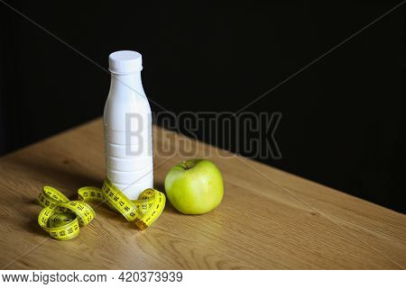 Diet.Diet concept.A bottle with a centimeter and an apple. Kefir. Milk.Losing weight on a low-calori