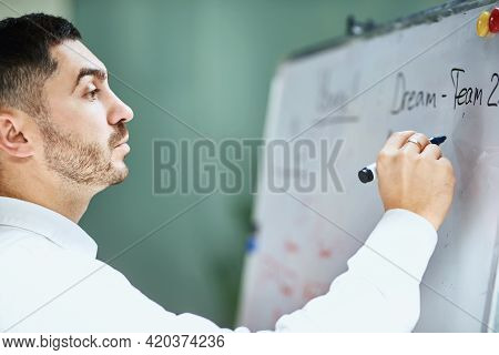 A Lecturer And Company Manager In A White Shirt Writes A Marker On A Flipchart. Plans And Is Ready T