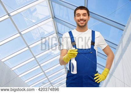 profession, cleaning service and people concept - happy smiling male worker or cleaner in overall and gloves with detergent over glasshouse background