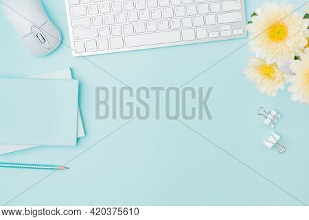 Flat Lay Blogger Or Freelancer Workspace With A Keyboard, Flowers In A Vase, Office Supplies On A Co