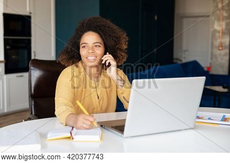 Cheerful African-american Young Woman Talking On The Smartphone, Using Laptop And Taking Notes At Ho