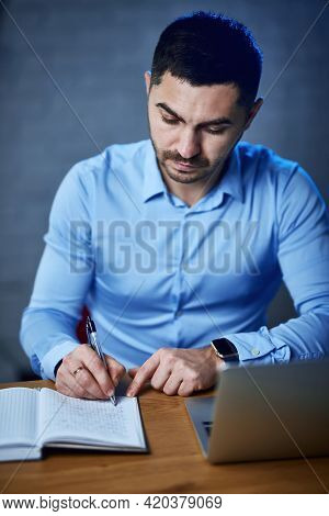 The Company Manager Writes Notes In The Notebook. Nearby Is A Laptop. Management And Planning. Onlin