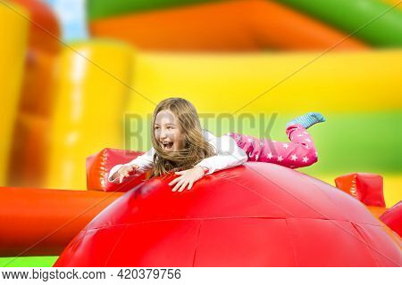 Happy Little Girl Having Lots Of Fun On A Inflate Castle While Jumping. Colorful Playground.
