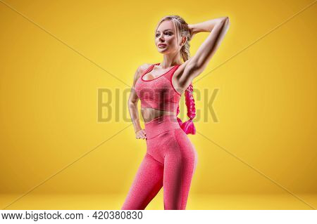 Portrait Of A Sexy Sportswoman Posing In The Studio On A Yellow Background. Fitness Concept. High Qu