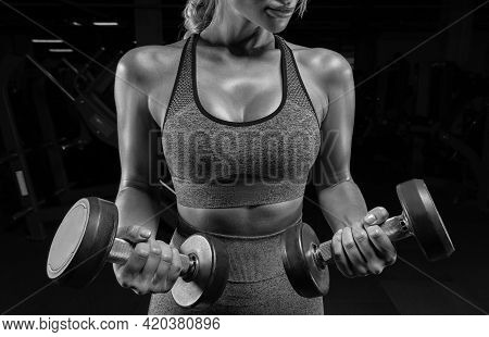 No Name Portrait Of A Girl In A Tracksuit Posing In The Gym With Dumbbells. Fitness Concept.