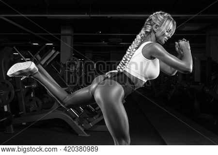 Portrait Of A Sexy Athlete Doing A Hamstring Exercise In The Gym. Fitness Concept.