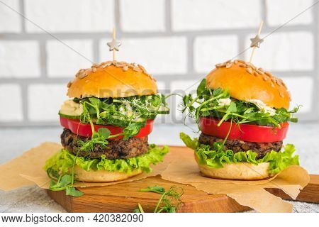 Vegetarian Burgers With Bean Burger And Fresh Vegetables On A Homemade Saucer On A Wooden Board On A