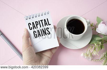 Businessman Holding A Card With Text Capital Gains. Business Concept