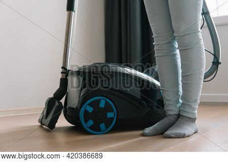 Technologies That Facilitate Wet Cleaning. Modern Household Appliances. Woman Standing Next To A Vac