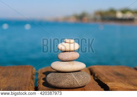 Pyramid Of Stones On A Wooden Pier By The Sea. Zen Concept. Blurred Background. Concept Of Harmony,