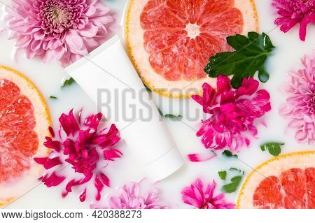 White Hand Cream Tube In Milk Bath With Pink Flowers And Grapefruit Slices. Organic Floral Or Citrus