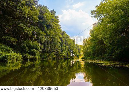 Summer Calm River Sunny Landscape. River Surface With Banks Of Densely Overgrown Green Trees With Th
