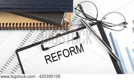 Text Reform On The Office Desk Table With Notebooks, Supplies,analysis Chart, On The White Backgroun