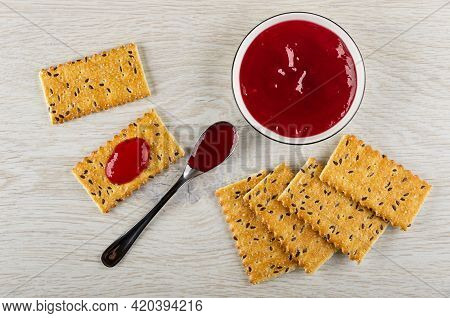 Cracker With Flax Seeds Poured Cherry Jam, Teaspoon With Jam, Bowl With Jam, Few Cookies On Wooden T