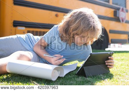Child Does School Homework Laying On Grass In The Park Near School Bus. School Kid Outdoor.
