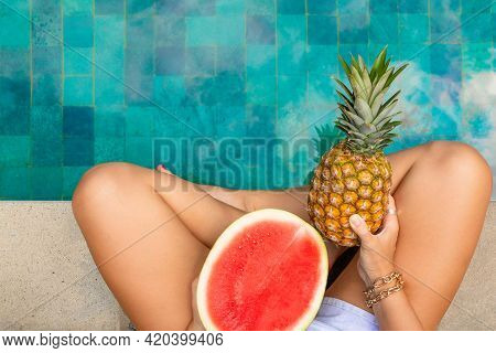 Womens Legs By The Pool With Tropical Fruits. Summer Concept.