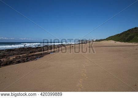 Stretch Of Beach With Vegetation With Layered Rocks On Shorline