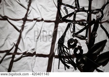Set Of Black Leather Sex Toys For Bdsm On The Background Of A Sheet In Bed. Whip, Handcuffs, Belt Be