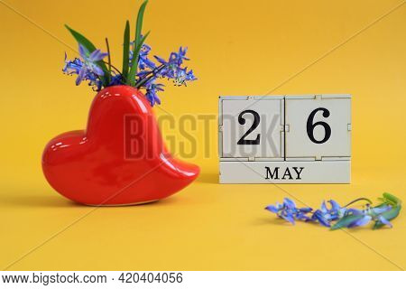 Calendar For May 26 : A Bouquet In A Heart-shaped Vase With Blue Flowers And The Number 26 On Cubes,
